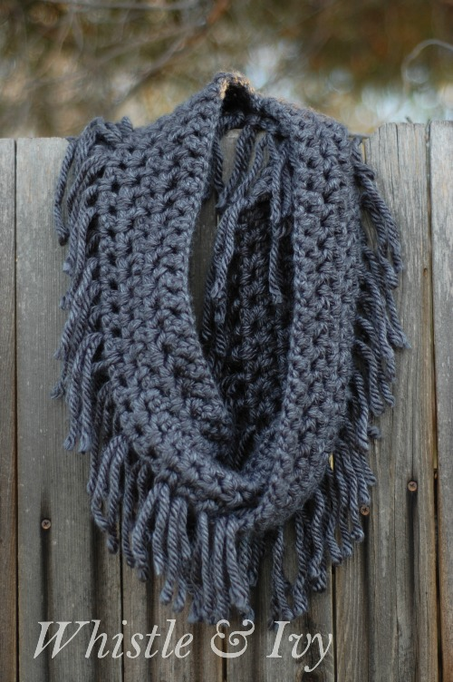 A charcoal gray simple chunky fringe crochet scarf turned into an infinity scarf draped on a fence