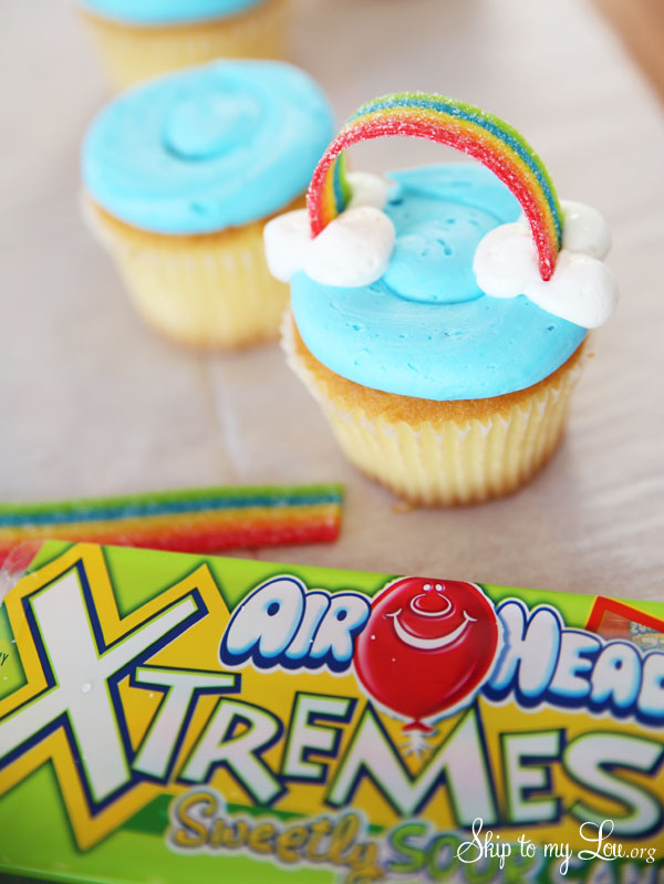 air heads xtremes rainbow inserted into the clouds, arching from one set of clouds to the other; a package of air heads xtremes candy rainbows is lying beside the cupcake