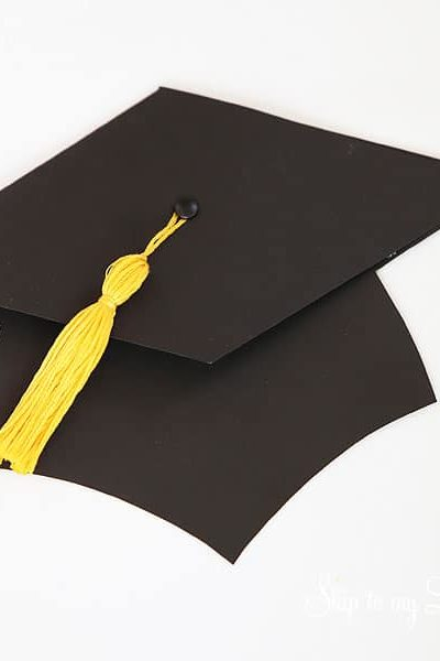 black grad hat with yellow tassel holds gift card