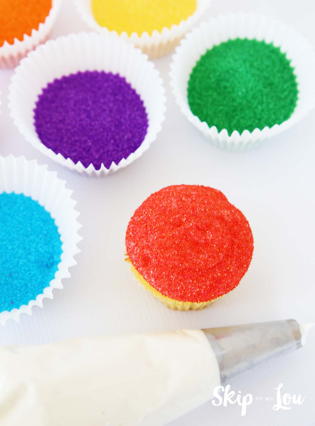 cupcake dipped in red sanding sugar, with a pastry bag with tip filled with white frosting, and jumbo baking cups filled with colored sanding sugar
