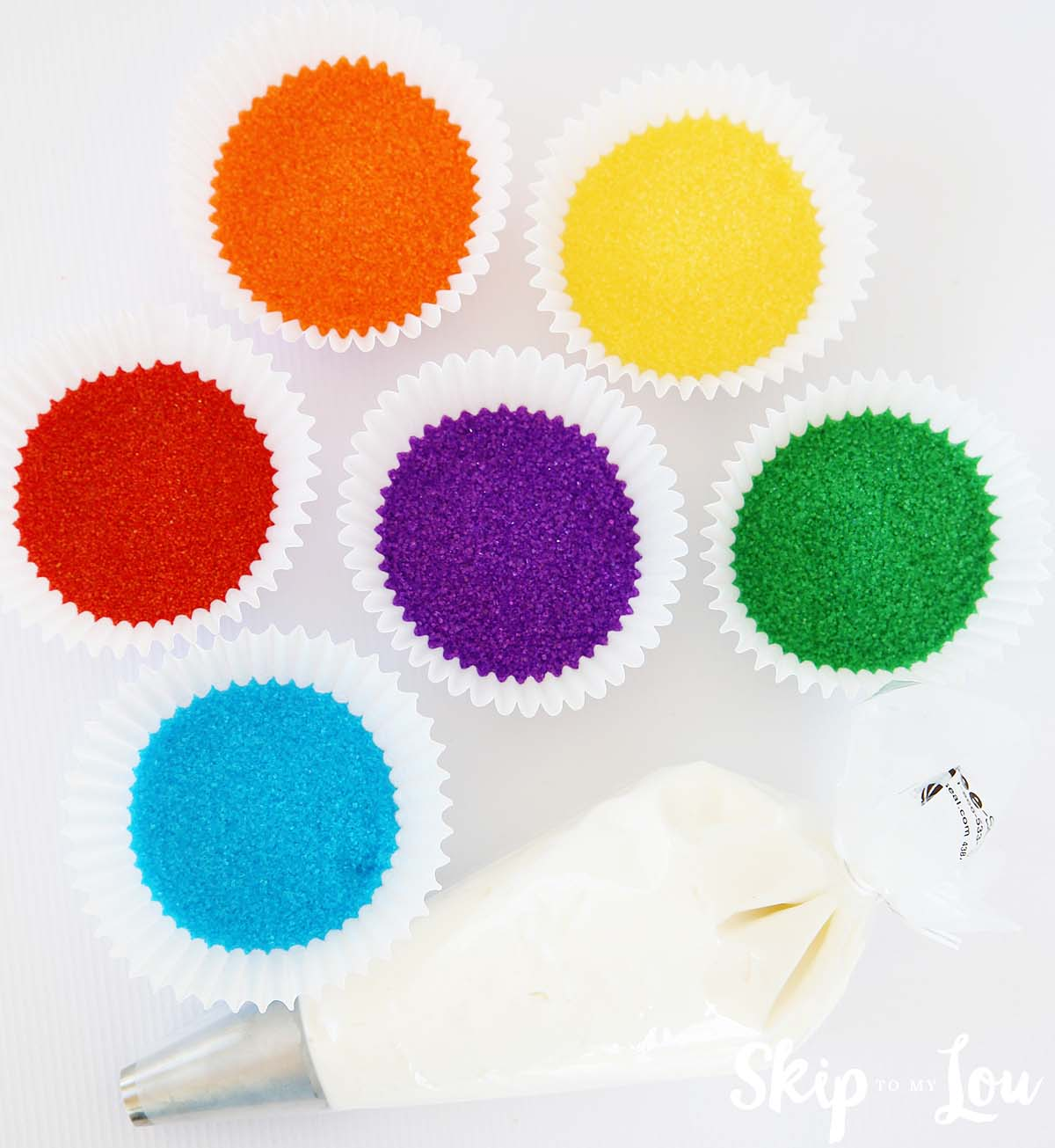 red, orange, yellow, blue, purple, and green sanding sugars in jumbo baking cups, and a piping bag with tip filled with white frosting