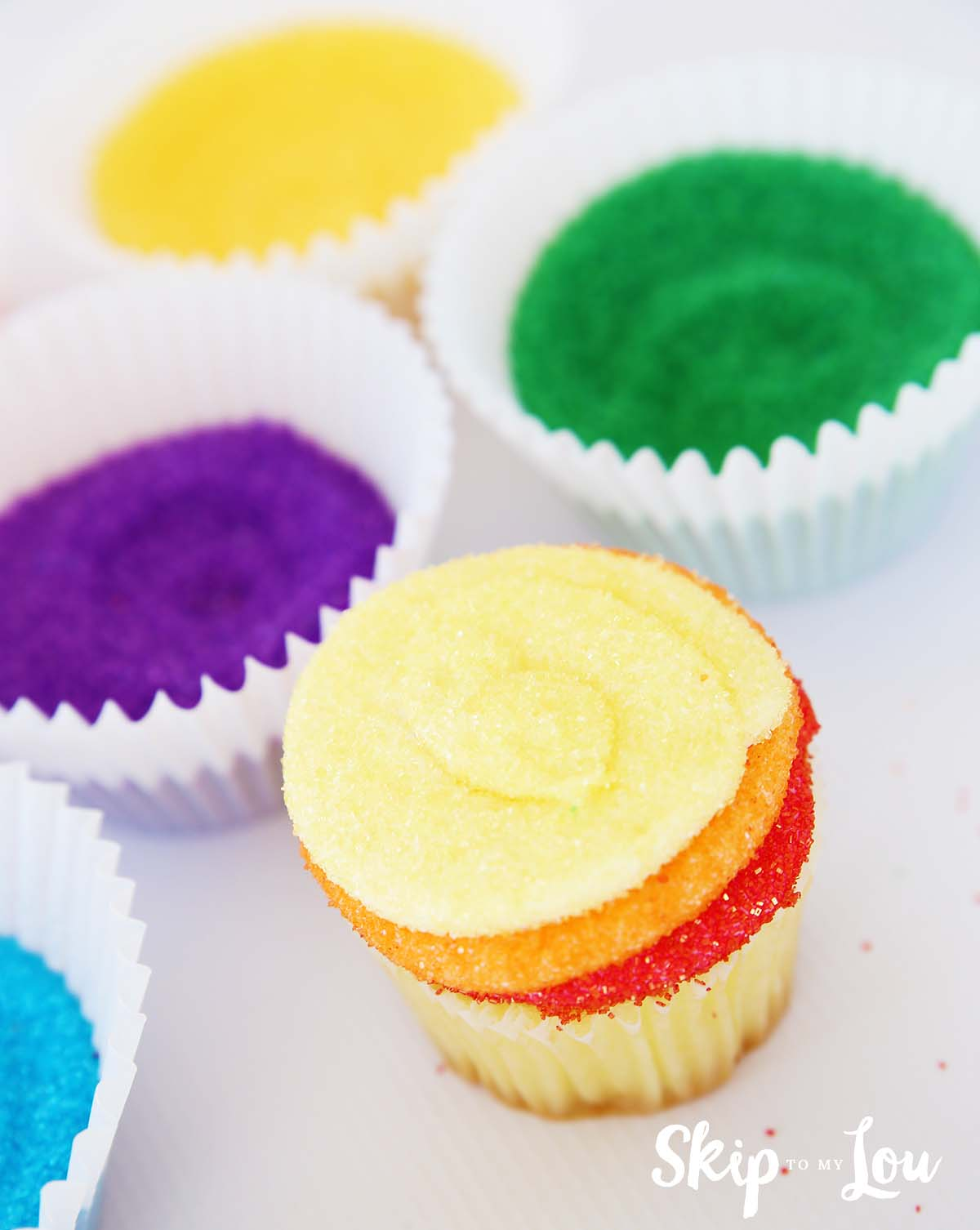 sanding sugar rainbow frosted cupcake with red, orange, and yellow layers