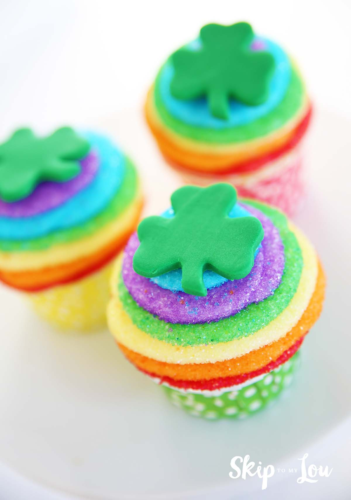 three sanding sugar rainbow shamrock decorated cupcakes