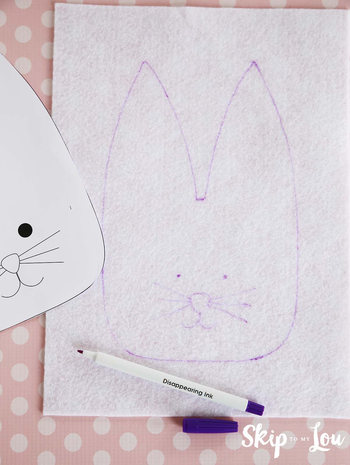 Easter bunny pattern, including the face, traced onto white felt with a purple disappearing fabric ink marker, the bunny template is resting to the left side of it