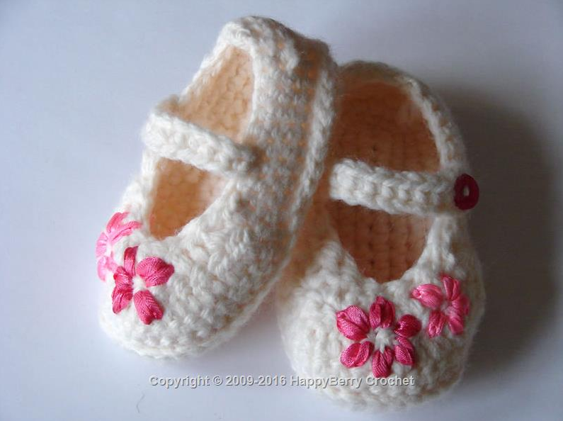 white baby booties with strap and dark pink embroidered flowers on toe