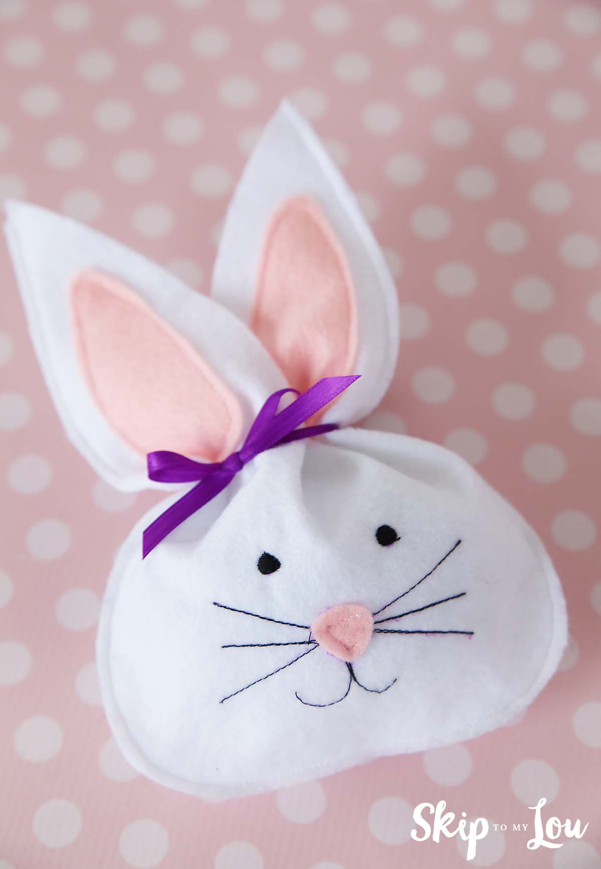white felt bunny treat bag laying on a pink polka dot table covering