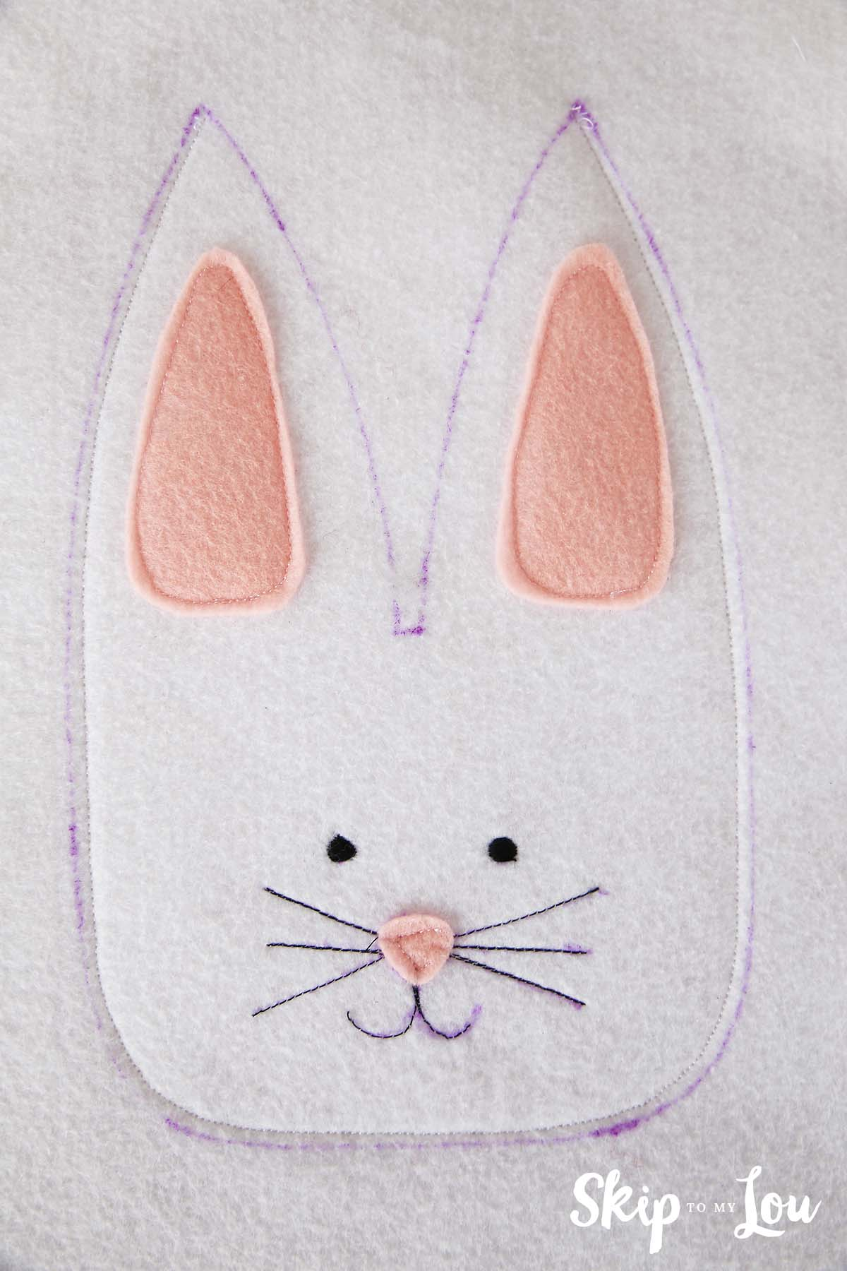 white felt sheet with bunny features sewn to a second layer of felt; the bunny head is sewn within the boundaries of the outline from the top of one ear going down around the face to the top of the second ear; the crevice between the ears is not sewn to leave an opening for the treats
