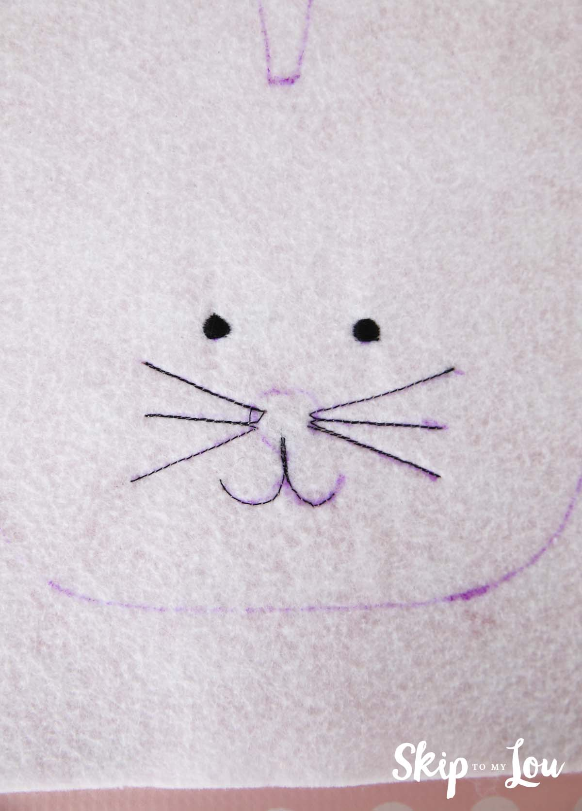 eyes, whiskers, and mouth sewn with black thread onto the white felt following the outline