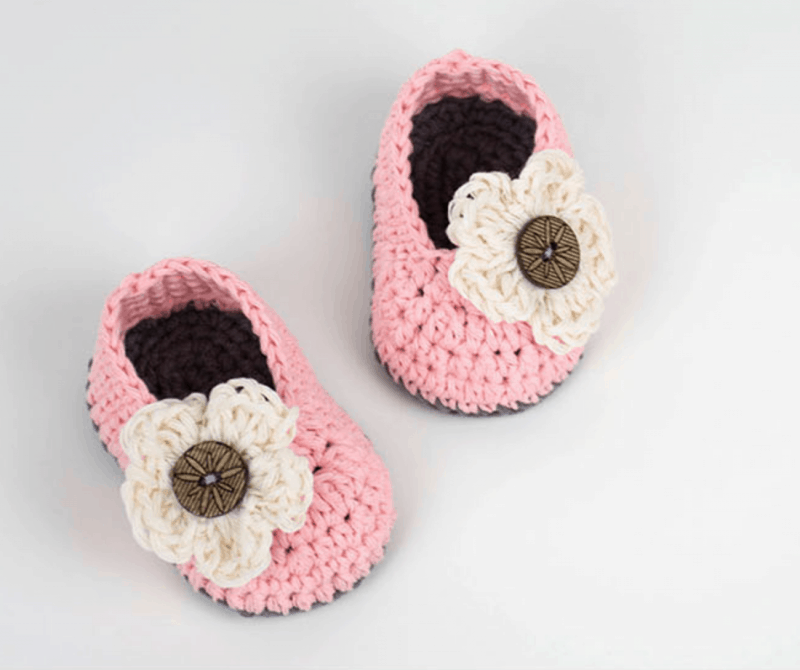 pink baby booties with white flower and gray bottoms