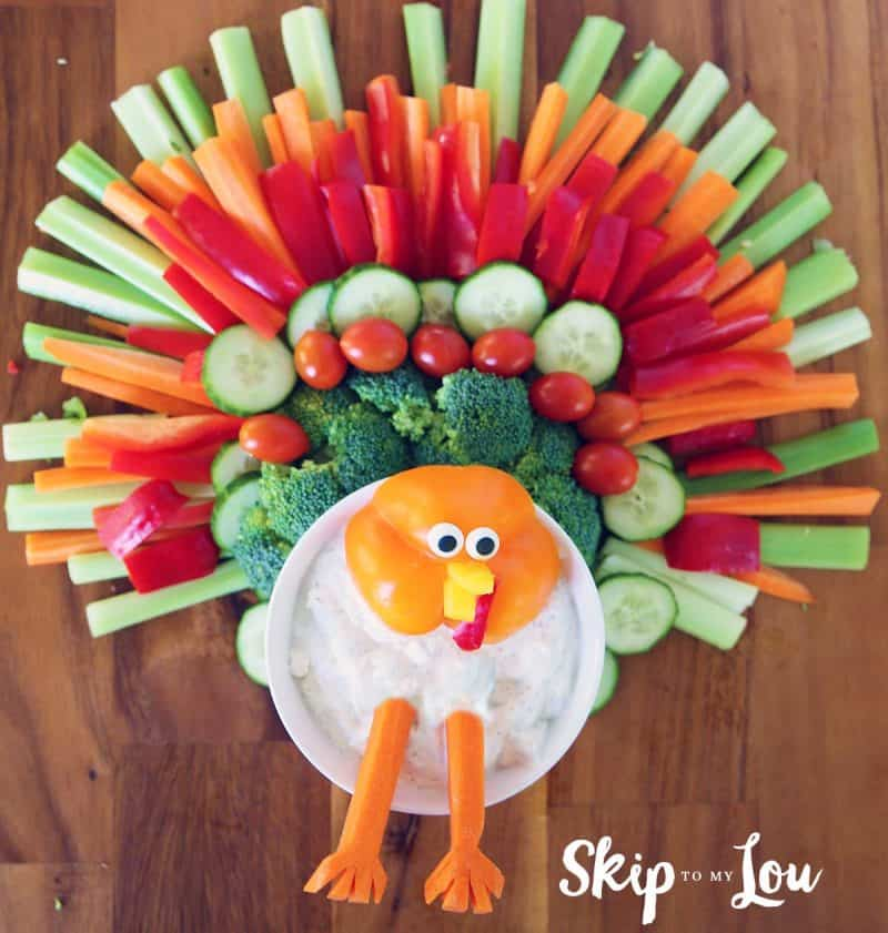 sliced vegetables put together to look like a turkey body is bowl of dip