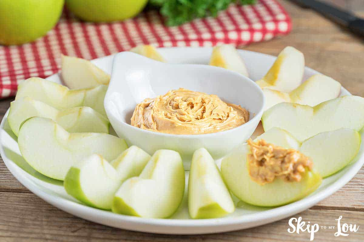 apple dip in white bold with granny smith apples on a plate around the dip
