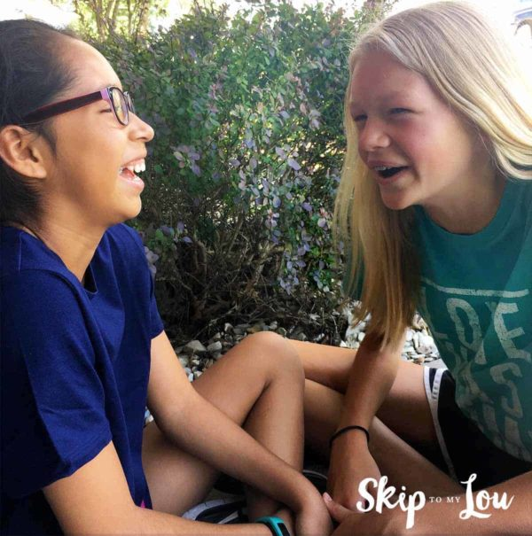 two girls laughing telling kids jokes