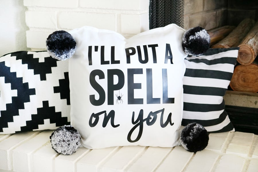 I'll put a spell on you pillow; the pillow is white with black letters and is decorating a white bench with tow other black and white decorative pillows