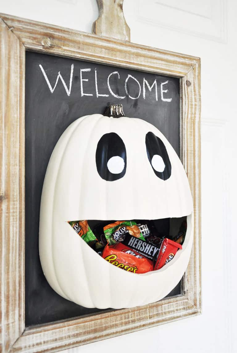 Candy door hanger - white pumpkin face basket filled with candy attached to a chalk board with a welcome writer in chalk