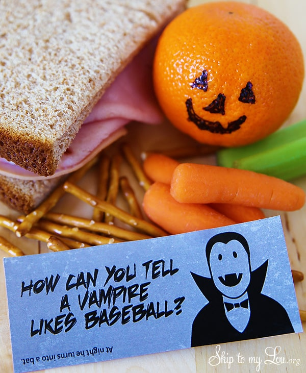 "Printable Halloween lunch box joke, ""How can you tell a vampire likes baseball?"" Packed in a lunch with a sandwich, orange with Jack-O-lantern face, pretzels, baby carrots and celery stick."