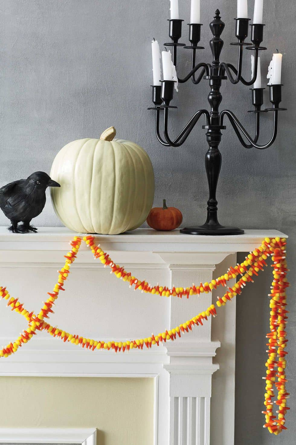 Candy corn garland strewn on a white mantel that is decorated with a black crow, white pumpkin, mini orange pumpkin, and candelabra