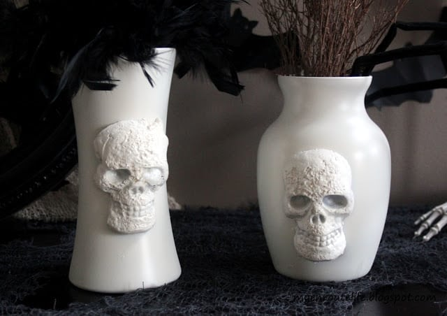 Two white skull vases with black flowers Halloween decorations a black table top