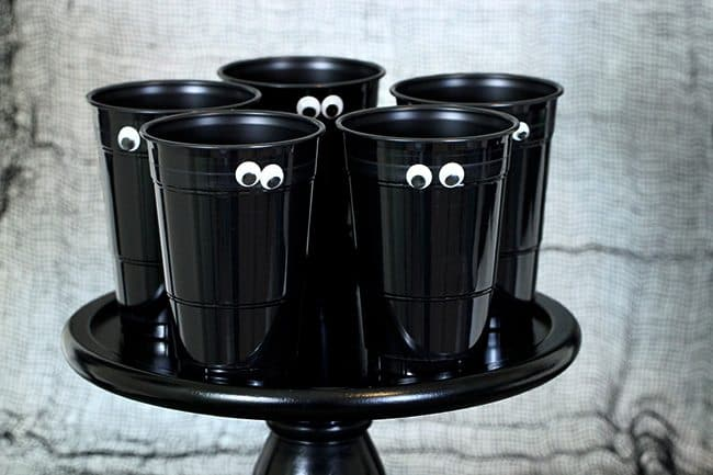 Halloween party decorations - spooky black cups with eyes sitting on a black cake platter