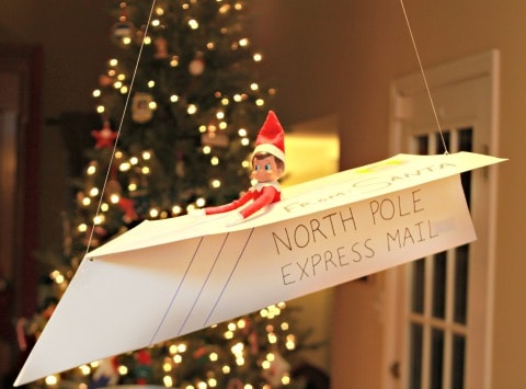 elf sitting in a paper airplane hanging from the ceiling