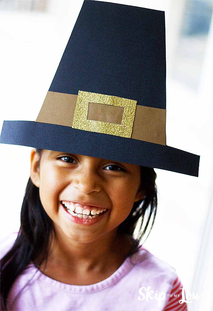 smiling little girl wearing a DIY pilgrim hat