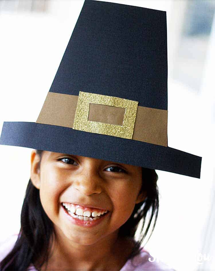 smiling little girl wearing her DIY pilgrim hat