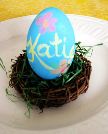 decorating easter eggs - blue chalkboard painted egg with the name Katie written on it with two flowers; the egg is setting on a bron straw basket with fake green grass like a nest