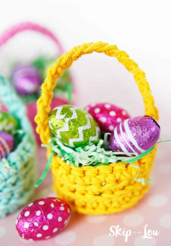 yellow crochet basket filled with fake green grass and three foiled wrapped mini chocolate eggs