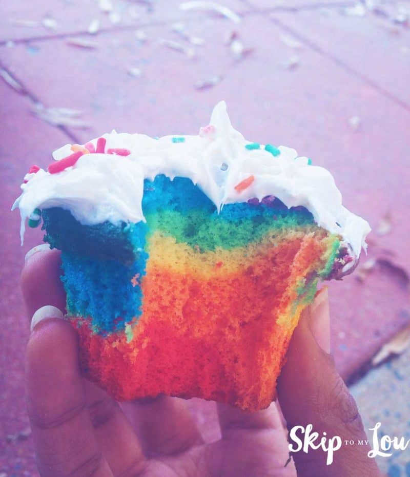 rainbow colored cupcake with bite out
