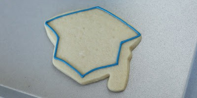 grad cap cookie with blue outline of frosting