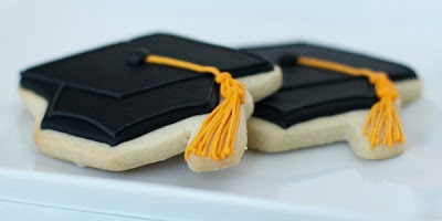 black grad cookies on white plate