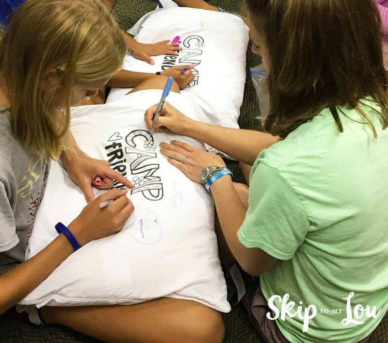 girls autographing camp pillow