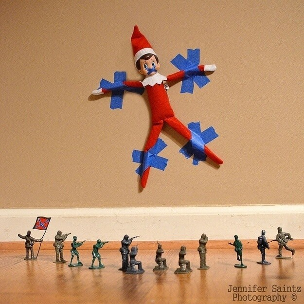 elf stuck to wall infront of a miniture firing squad