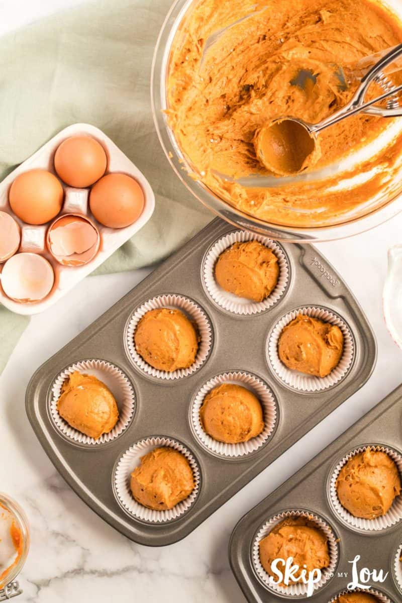 pumpkin muffin batter scooped into a prepared mufin pan, a large stainless steel cookie scoop was used to scoop the batter