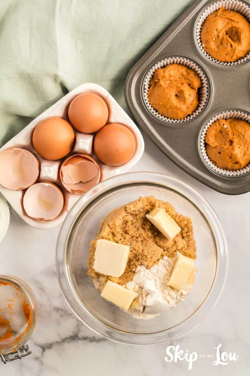 streusel topping ingredients - flour, brown sugar and butter place in a small mixing bowl with a muffin tin and muffin batter set to the side waiting for streusel to be added