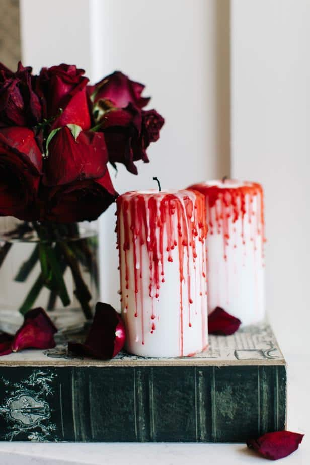 two bloody candles with dying red roses on a table top