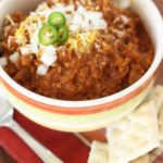 chili recipe in bowl with onions jalpenos crackers on the side