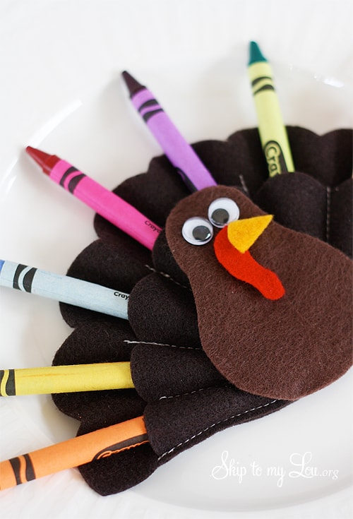 felt turkey holder with crayons laying on white plate
