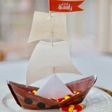 paper origami mayflower ship on white plate