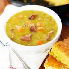split pea soup in white bowl cornbread on side