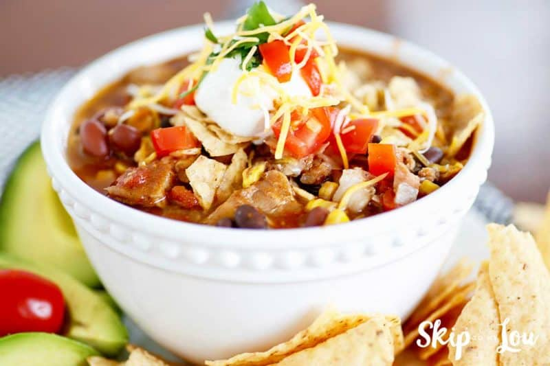 slow cooker chicken taco soup with avacado and tortilla chips on the side