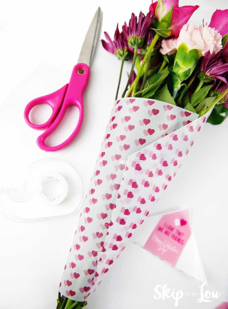 scissors tape flowers wrapped in printed heart paper gift tag