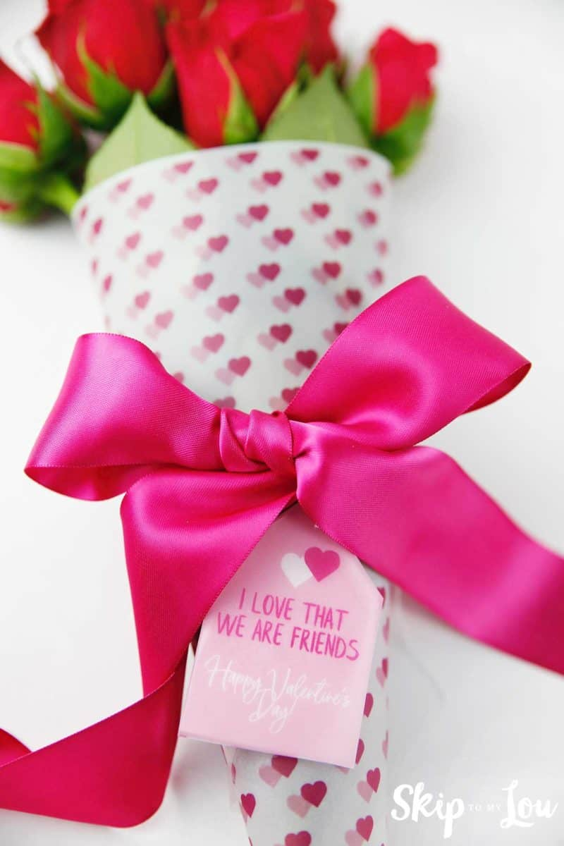 flowers wrapped in heart paper tied pink bow