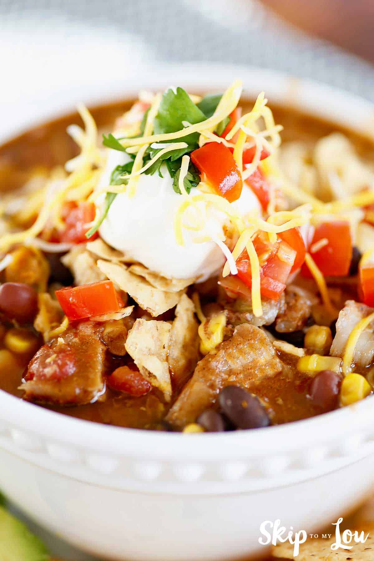 chicken taco soup topped with sour cream and tortilla chips