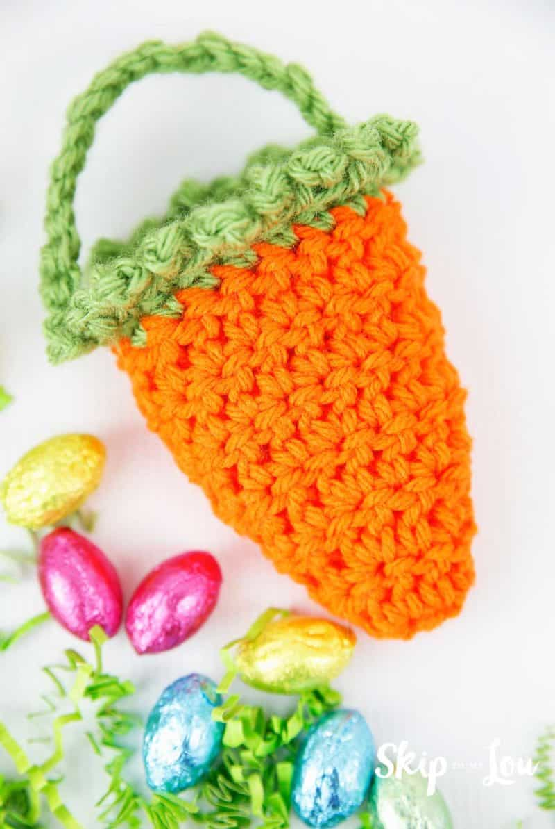 crochet carrot basket with green paper shred and foil covered chocolate eggs beside