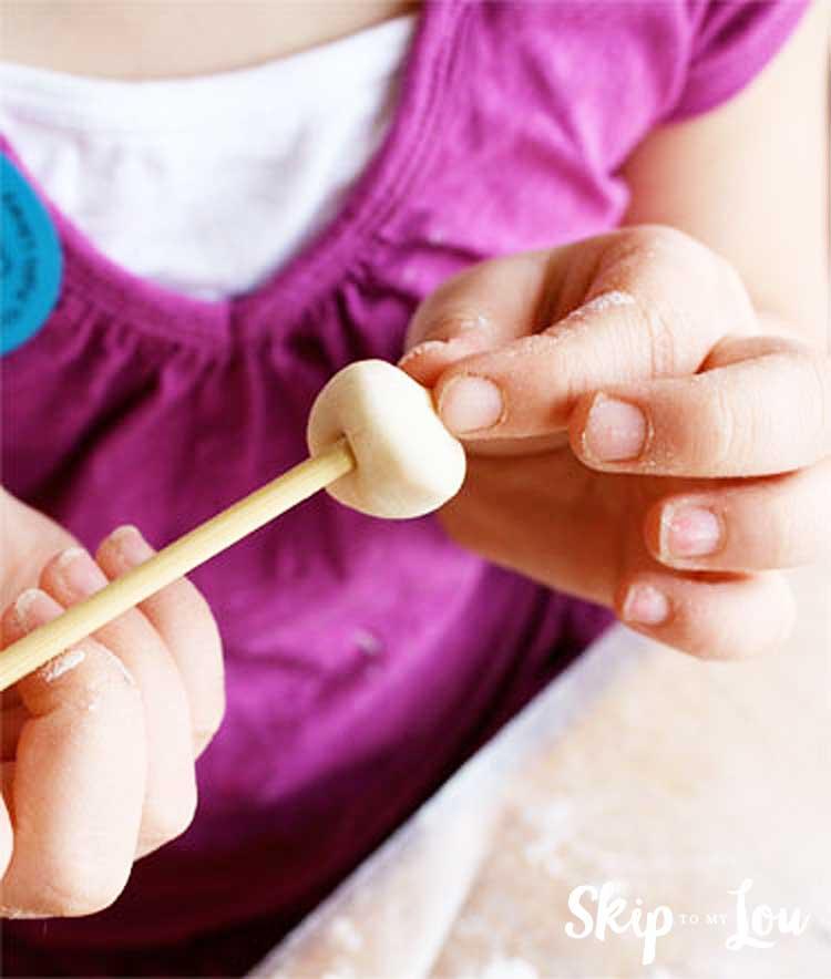 child forming salt dough bead