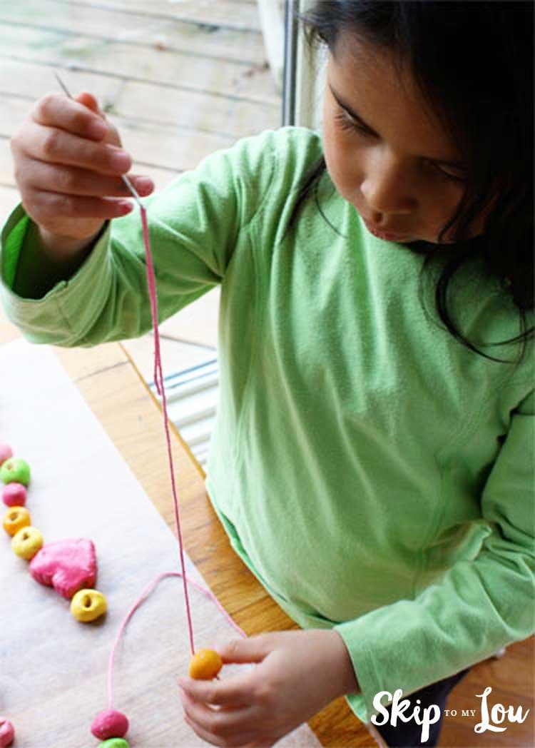 child putting salt dough beads on string