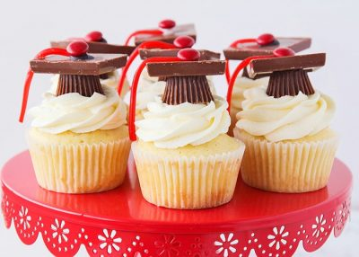 white cupcakes with white frosting and candy grad hat with red tassel on red cake stand