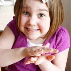 child rolling salt dough between hands
