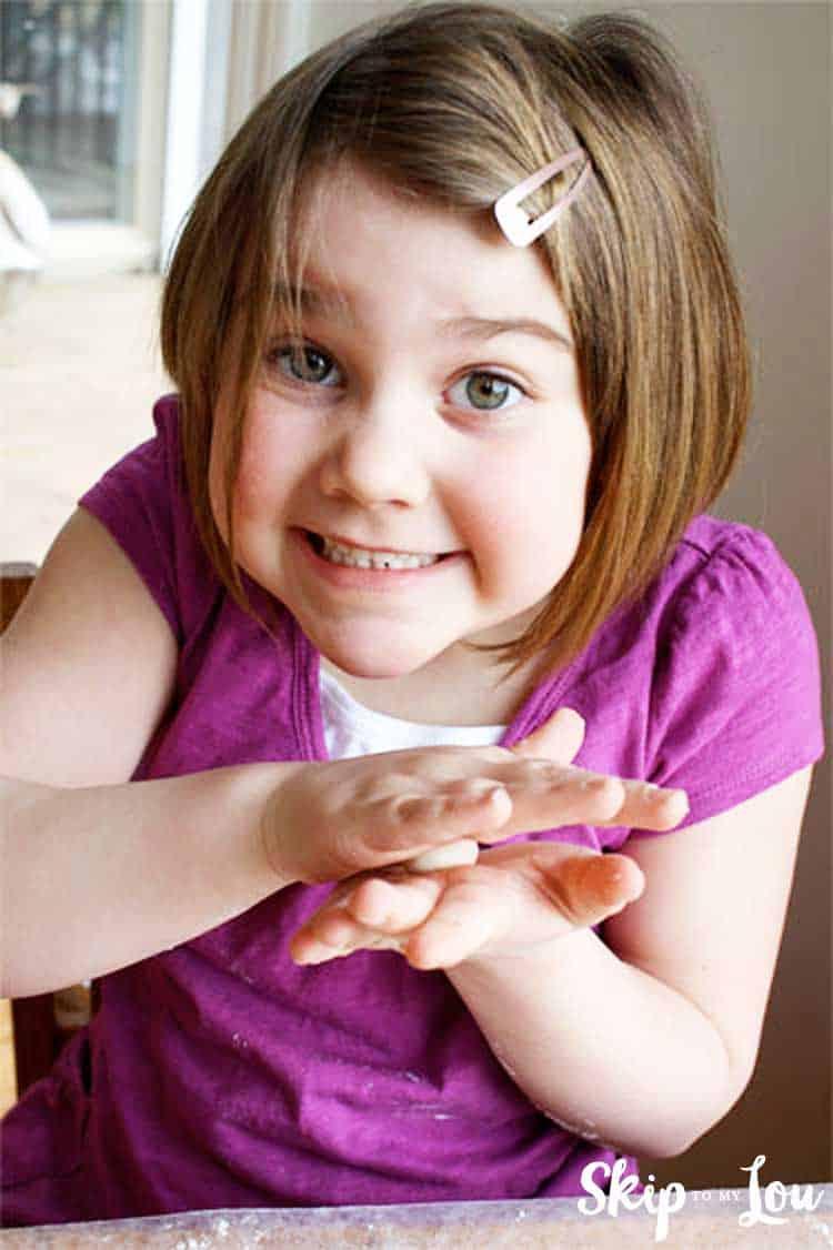 child rolling salt dough between hands