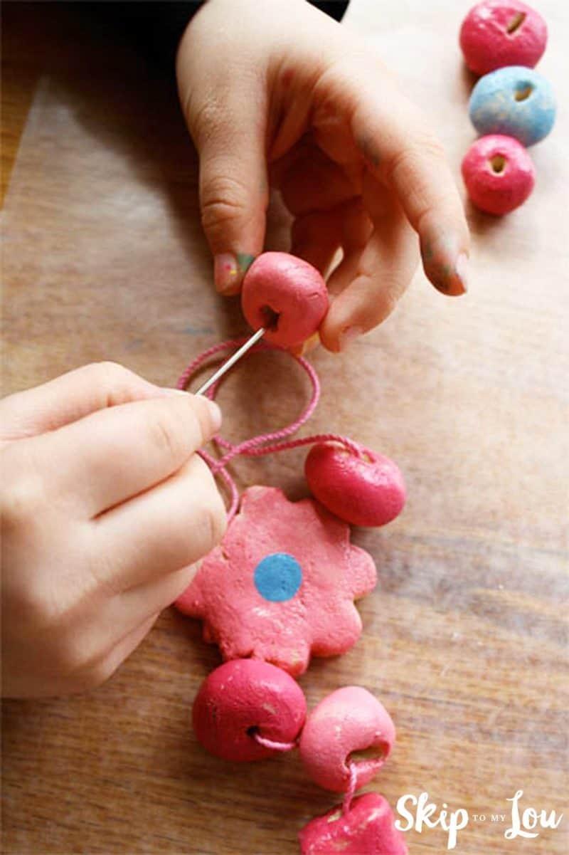 hands stringing salt dough beads